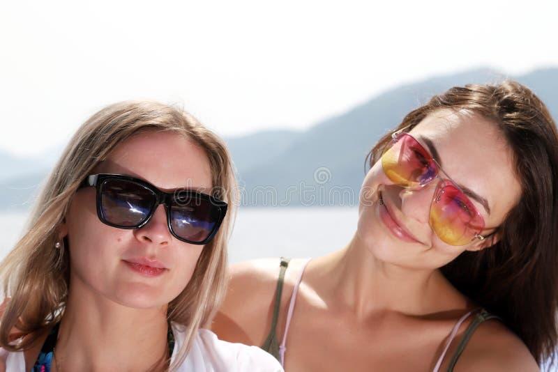 Två härliga flickor nära havet och bergbakgrunden royaltyfria bilder