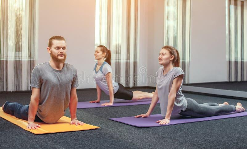 Två härliga flickor och mannen gör yoga i den sportmitten och brunnsorten royaltyfri fotografi