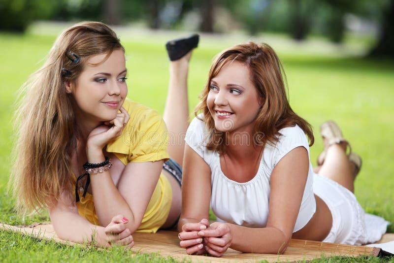Två härliga flickor som hänger i parkera arkivfoton