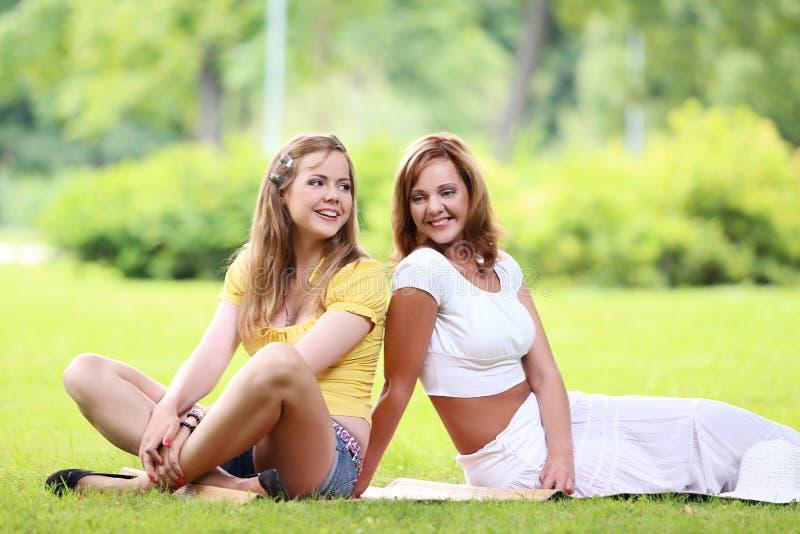 Två härliga flickor som hänger i parkera royaltyfri foto