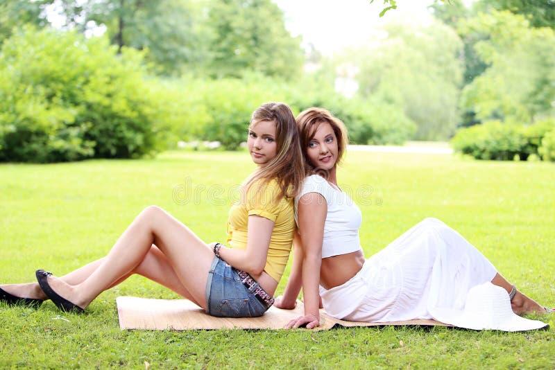 Två härliga flickor som hänger i parkera royaltyfria bilder