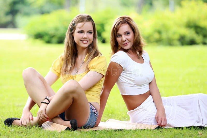 Två härliga flickor som hänger i parkera arkivfoto