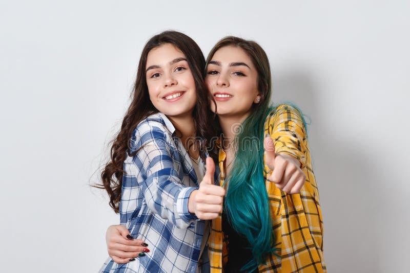 Två härliga flickor som ler upp och visar tummar På vitbakgrund royaltyfri bild