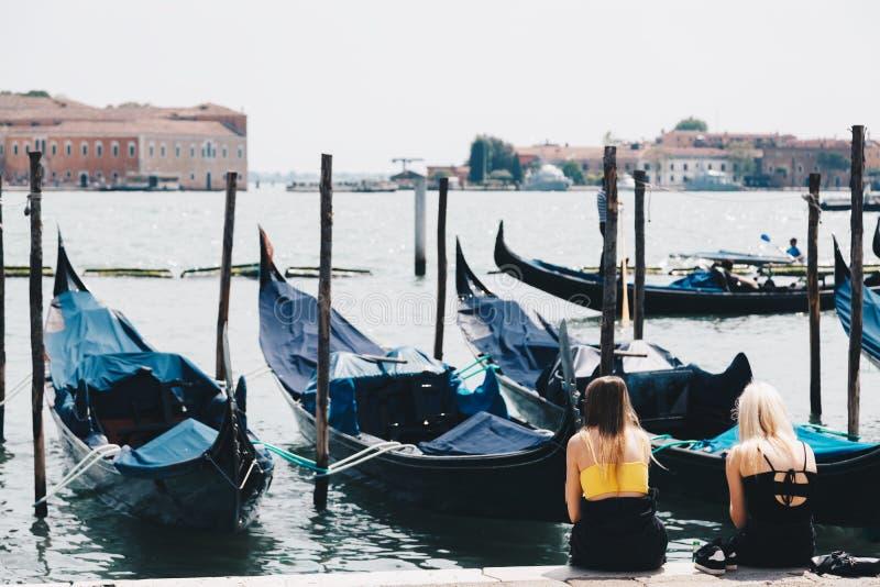 Två härliga flickor som ser seascape i venice med gondoler royaltyfri foto