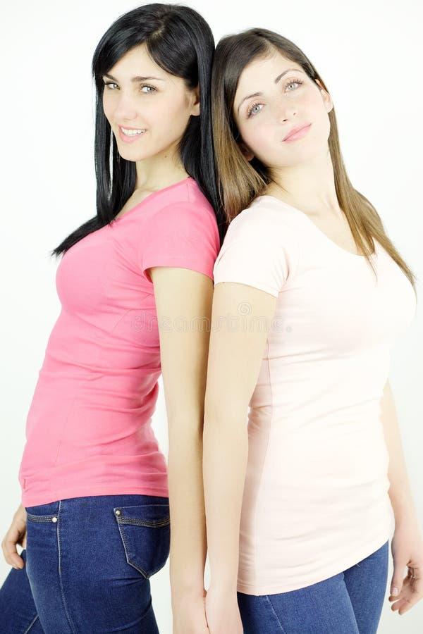Två härliga flickor som visar starkt kamratskap som ser kameran arkivfoto