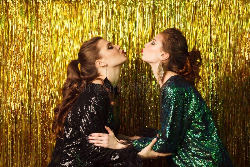 Två härliga gladlynta kvinnor på partiet på mousserande backgroun royaltyfri foto