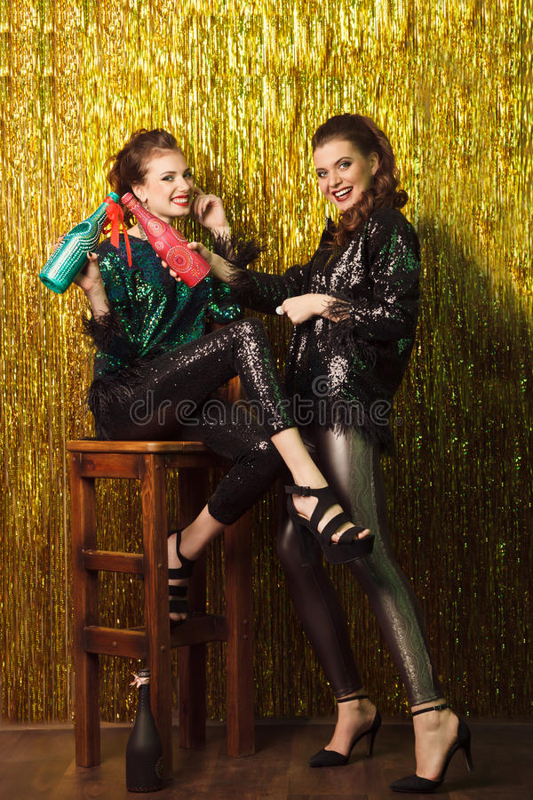 Två härliga gladlynta kvinnor på partiet på mousserande backgroun royaltyfri bild