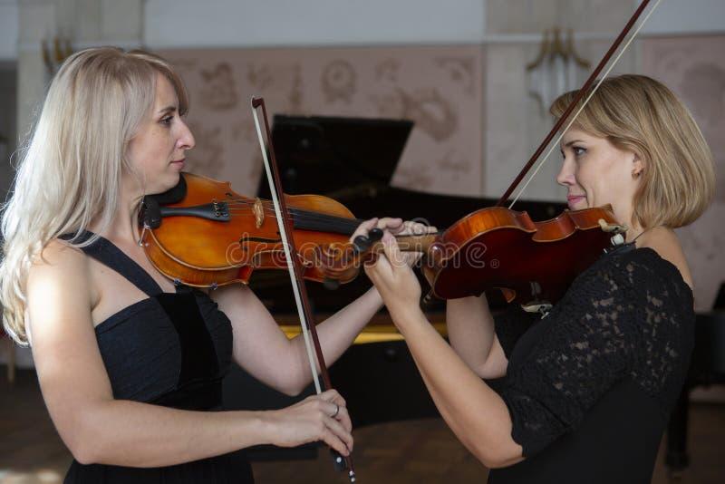 Två härliga kvinnliga violinister som spelar fiolen royaltyfria bilder