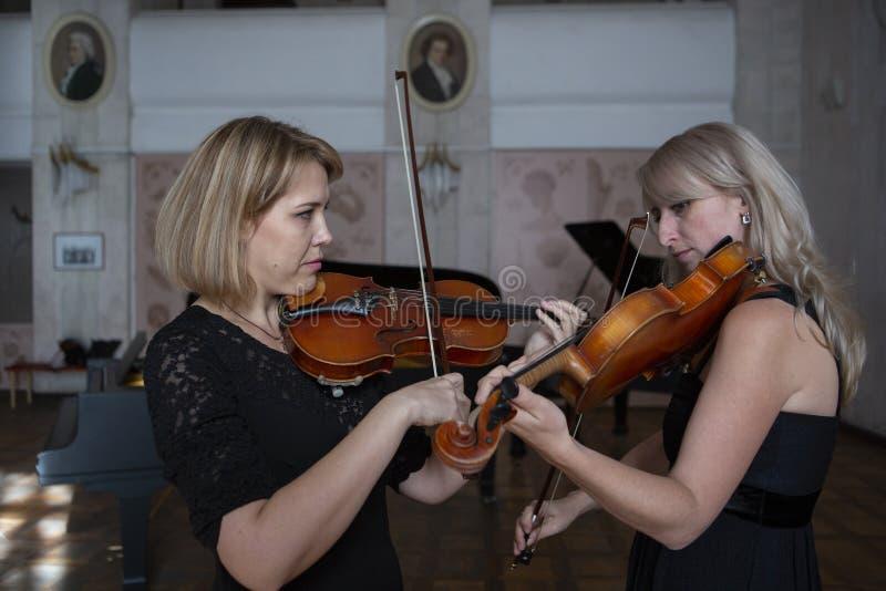 Två härliga kvinnliga violinister som spelar fiolen royaltyfria foton