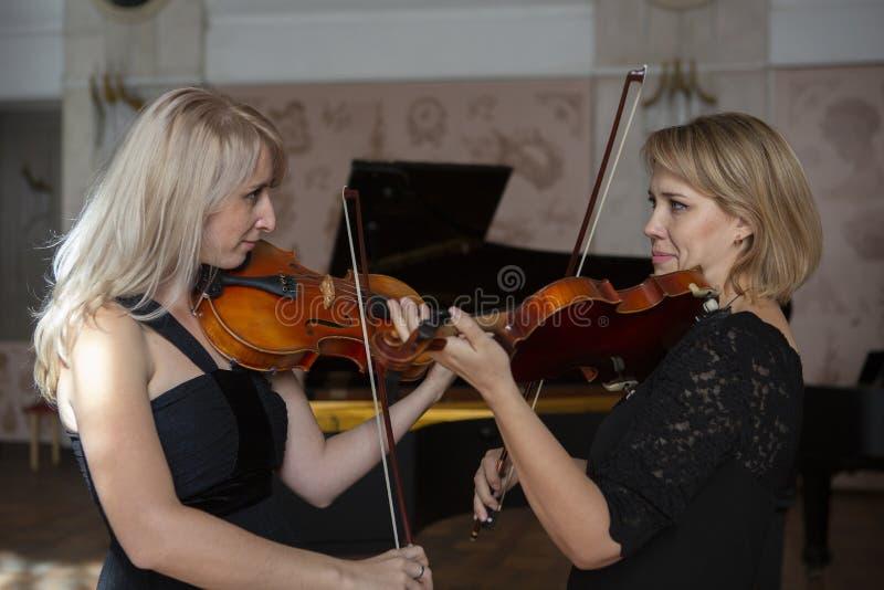 Två härliga kvinnliga violinister som spelar fiolen arkivfoton