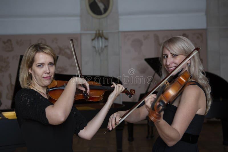 Två härliga kvinnliga violinister som spelar fiolen arkivbild