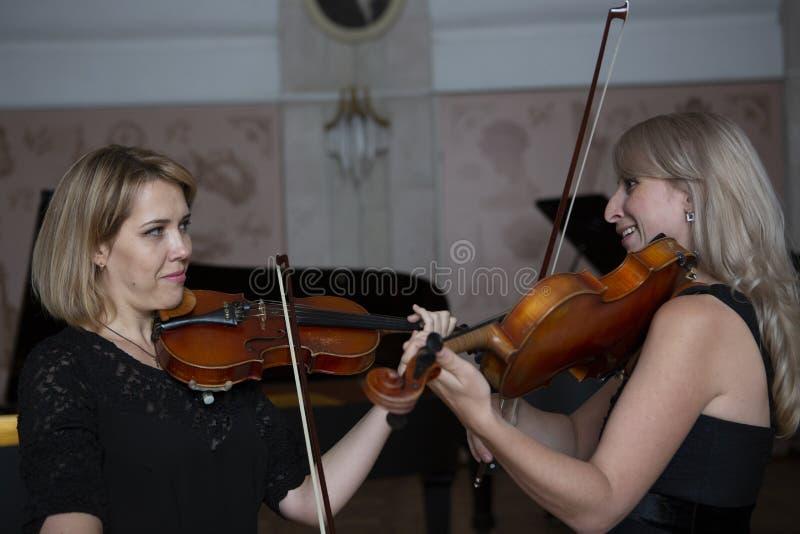 Två härliga kvinnliga violinister som spelar fiolen royaltyfri bild