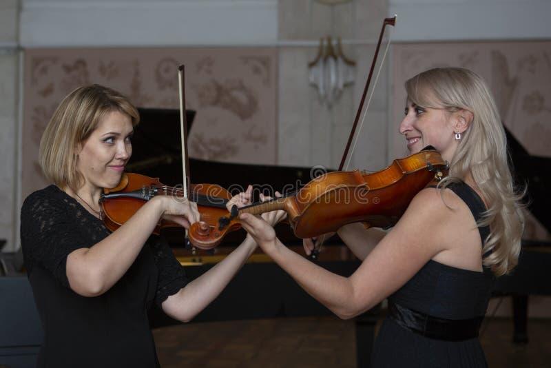 Två härliga kvinnliga violinister som spelar fiolen fotografering för bildbyråer