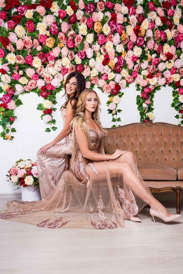 Två härliga kvinnor i klänningar som sitter på tappningsoffan över colo royaltyfri bild