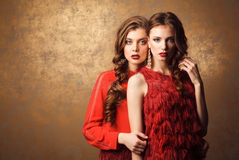 Två härliga kvinnor i röda klänningar Perfekt makeup och frisyr royaltyfri bild