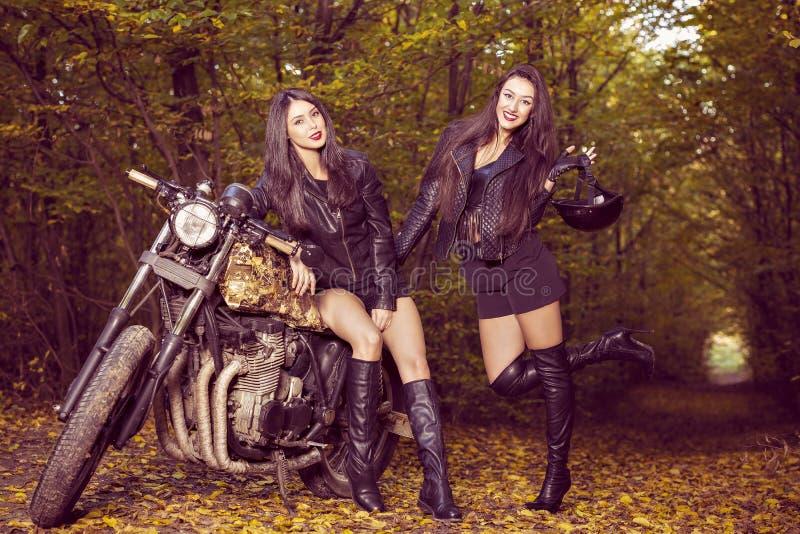 Två härliga kvinnor som är passionerade om motorcyklar arkivfoton