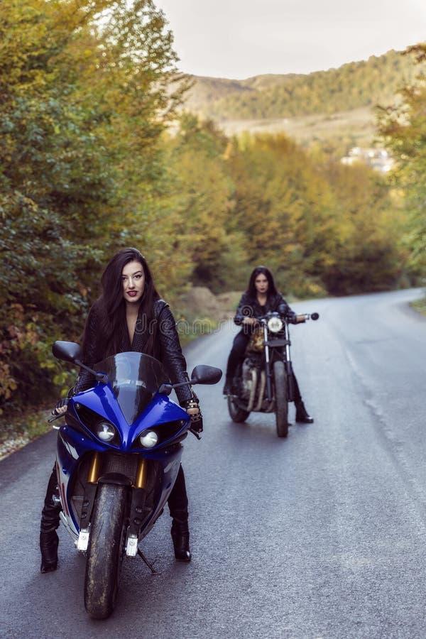 Två härliga kvinnor som är passionerade om motorcyklar royaltyfri foto