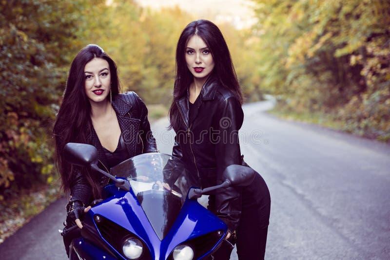 Två härliga kvinnor som är passionerade om motorcyklar royaltyfria foton