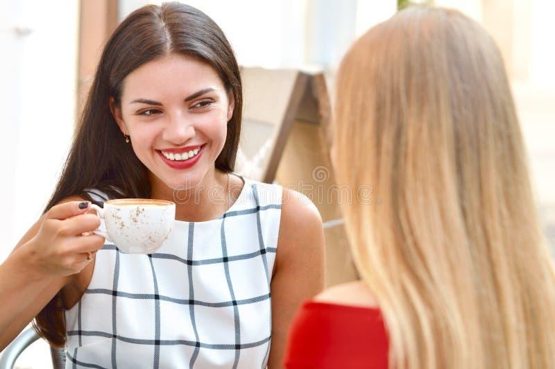 Två härliga kvinnor som dricker kaffe på yttersidastången royaltyfria bilder