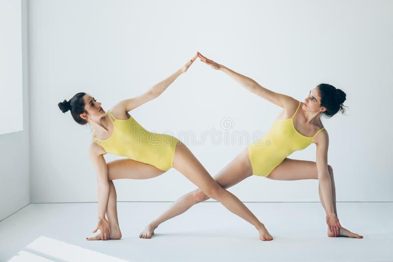 Två härliga kvinnor som gör fördjupad sidovinkel för yoga asanaen, poserar arkivfoton