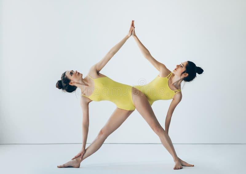 Två härliga kvinnor som gör fördjupade triangeln för yoga asanaen, poserar royaltyfria foton