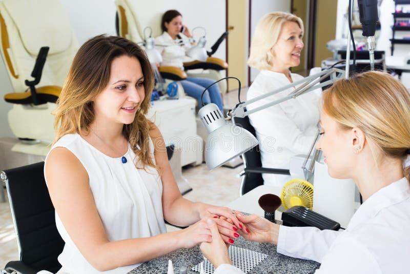 Två härliga kvinnor som gör manikyr royaltyfria foton