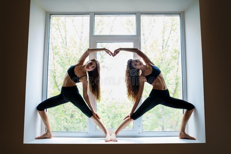 Två härliga kvinnor som gör symbol för hjärta för yogaasanavisning på seger arkivbild