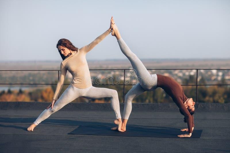 Två härliga kvinnor som gör yogaasanavirabhadrasana på taket arkivfoto