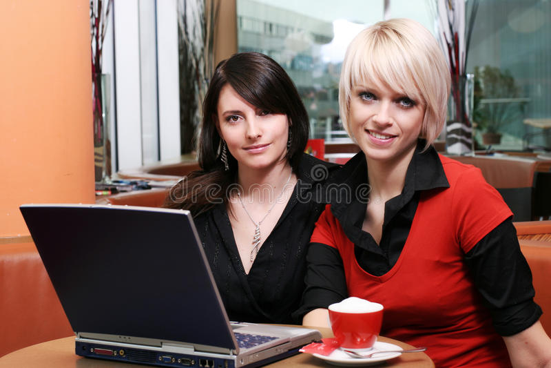 Två härliga kvinnor som möter över kaffe royaltyfri bild