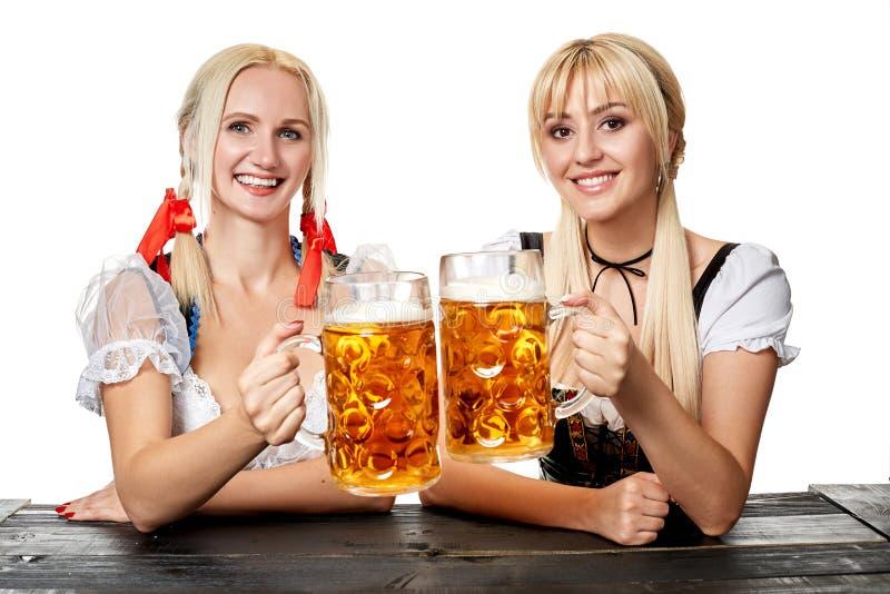 Två härliga kvinnor som rymmer ett exponeringsglas av öl, medan sitta på en trätabell på en vit bakgrund i studion royaltyfria foton