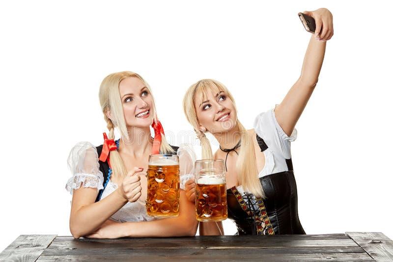 Två härliga kvinnor som rymmer ett exponeringsglas av öl, medan sitta på en trätabell på en vit bakgrund i studion royaltyfri fotografi