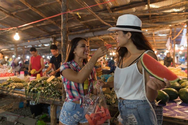 Två härliga kvinnor som smakar vattenmelon på traditionell gatamarknad i Asien ung flickaturister som köper på nya frukter royaltyfria bilder