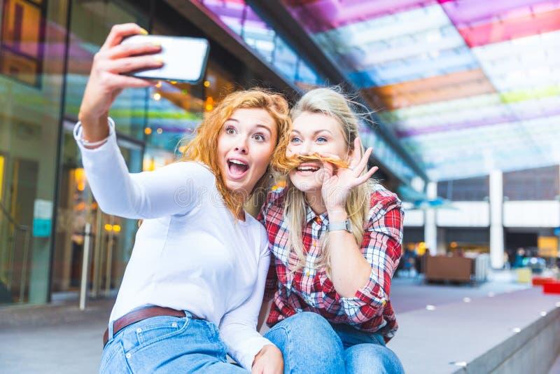 Två härliga kvinnor som tar en rolig selfie arkivfoton
