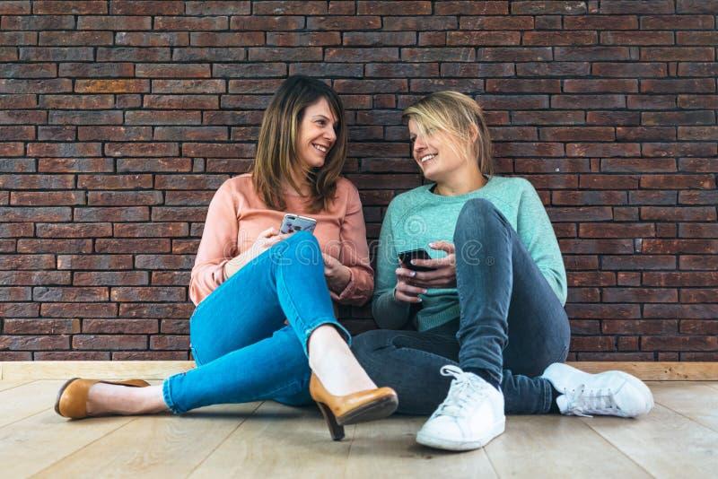 Två härliga le kvinnor som sitter på golvet med en telefon royaltyfri fotografi