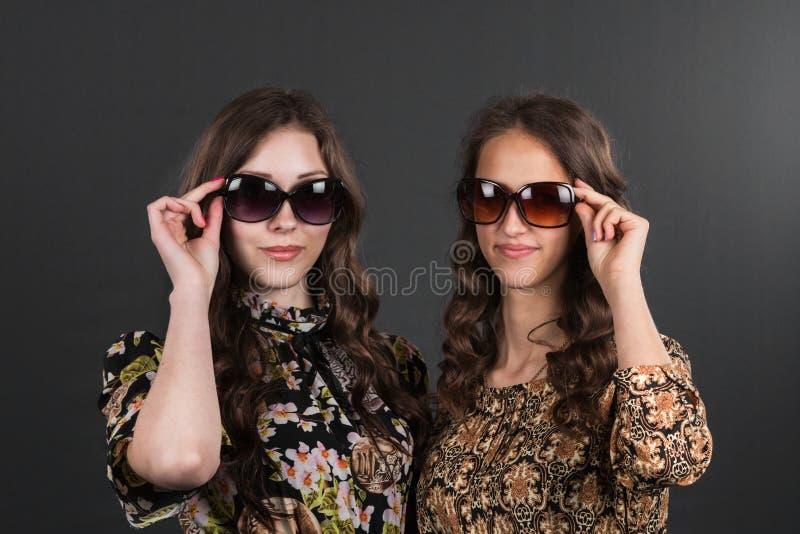 Två härliga lyckliga flickor i solglasögon på den gråa bakgrunden royaltyfri fotografi