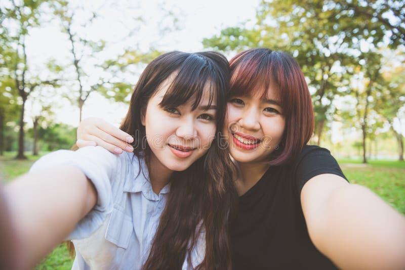 Två härliga lyckliga unga asiatiska kvinnavänner som har gyckel på, parkerar tillsammans och tar en selfie royaltyfria bilder