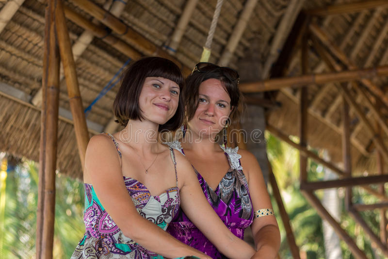 Två härliga lyckliga unga flickor som sitter i en trägazebo på den soliga dagen och ha gyckel, att le och att skratta tropiskt arkivfoton