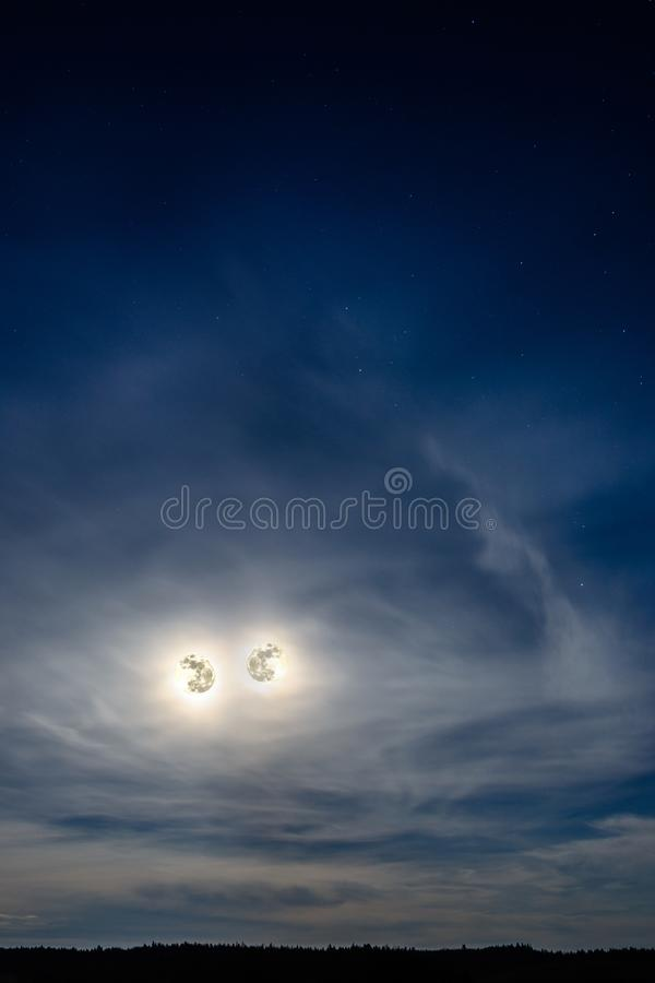 Två härliga månar ser oss från himlen arkivfoton
