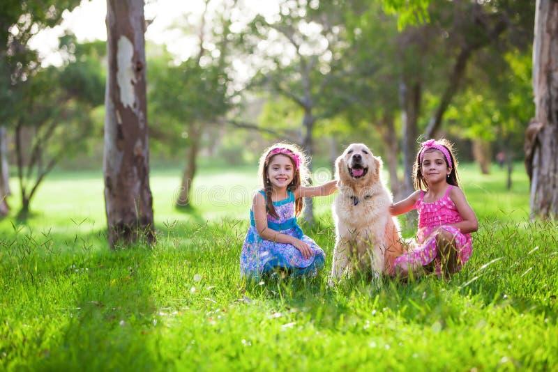 Två härliga små flickor och hundvängolden retriever i th royaltyfri bild