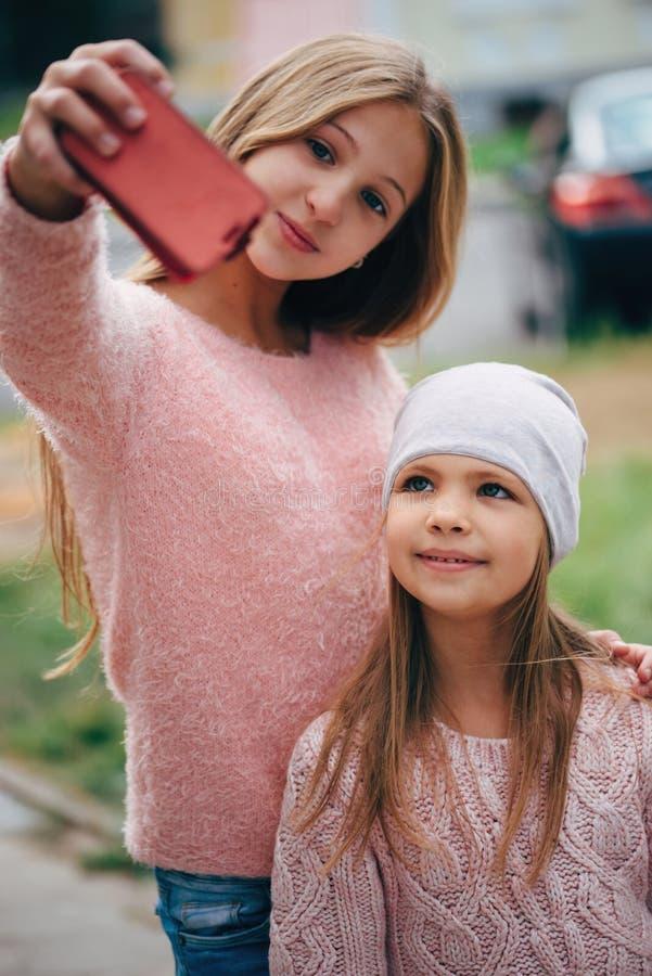 Två härliga små flickor som gör selfie royaltyfri bild