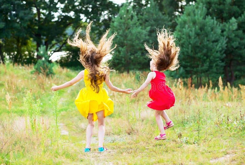 Två härliga små flickor som hoppar och dansar på solig sommar D royaltyfri fotografi