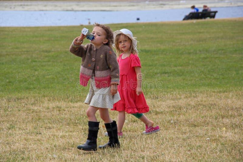 Två härliga stilfulla små flickor går i StJames'sen parkerar royaltyfri foto
