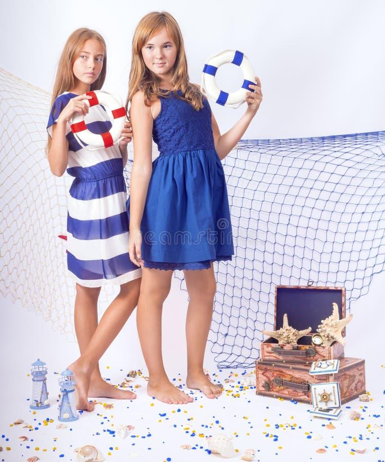 Två härliga tonåriga flickor som står med livboj arkivbilder