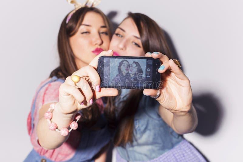 Två härliga tonåringar för brunettkvinnor (flickor) spenderar tidtogeth fotografering för bildbyråer