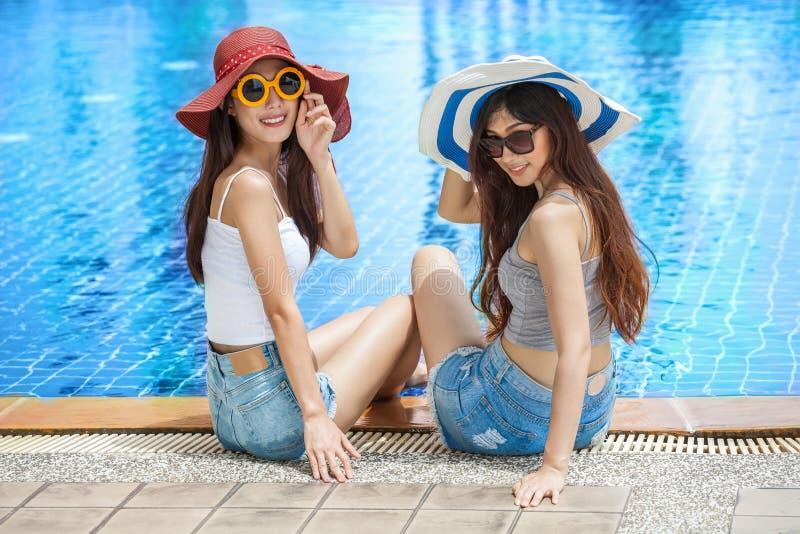 två härliga unga asiatiska kvinnor i stor sommarhatt och solglasögon som sitter på kanten av simbassängen med fot i vatten arkivbild