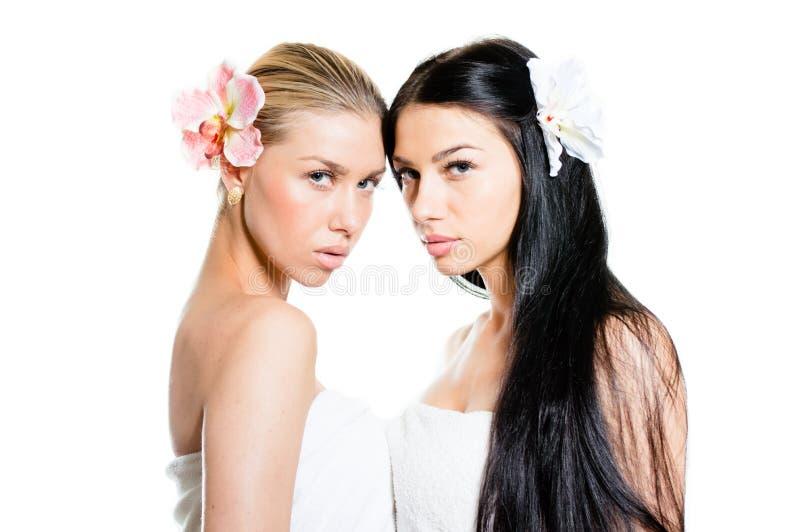 Två härliga unga brunettkvinnor med perfekt hud, blåa ögon och blomman för lilja för lyxigt smyckenörhänge den hållande & att se  arkivfoton