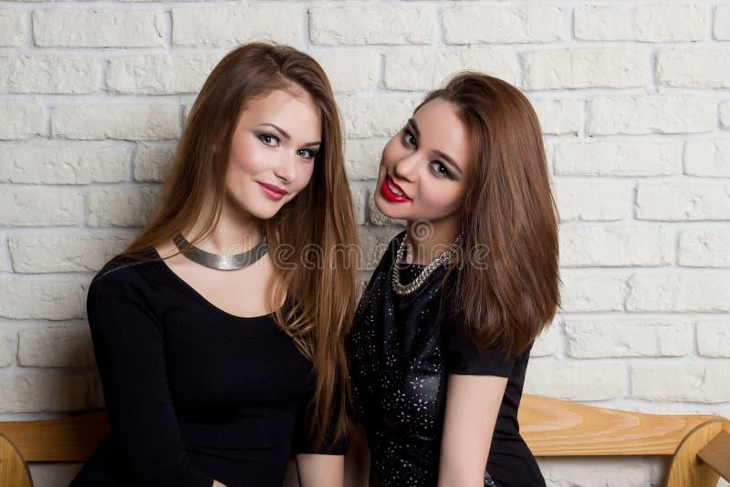 Två härliga unga flickor i svarta klänningar sitter på bänken och skvallrar royaltyfria foton