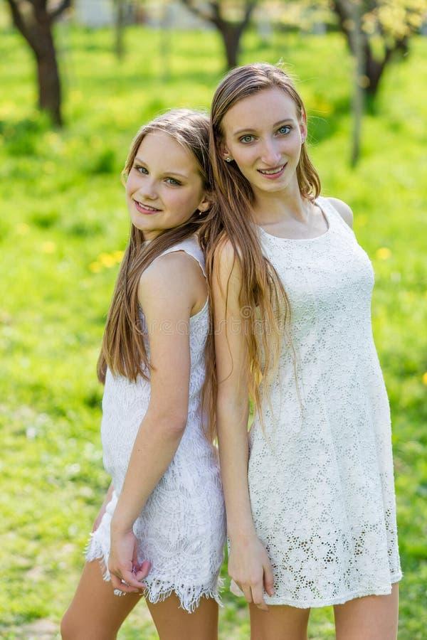 Två härliga unga flickor i vita klänningar i sommar arkivbilder