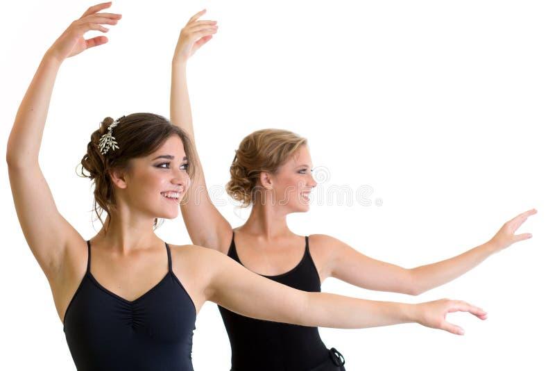 Två härliga unga flickor som gör övning eller tillsammans dansar arkivbild