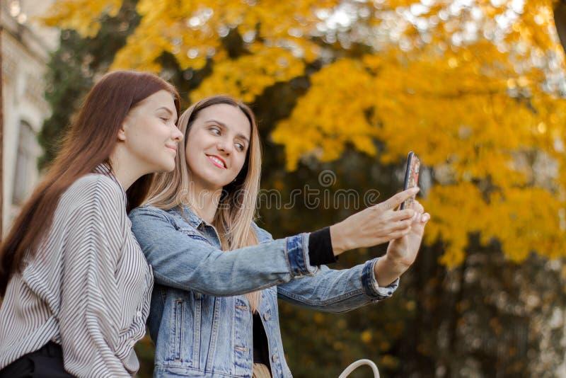 Två härliga unga flickor som tar selfie på telefonen i hösten, parkerar royaltyfri fotografi